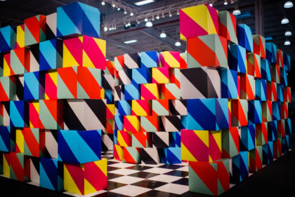 Large scale installation using stacked cardboard boxes with colorful patterns