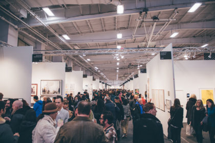 Art on paper fair in New York City, crowded fair space, visitors looking at artworks