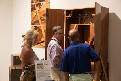 Market Art & Design, group of three people talking about an exhibited artwork