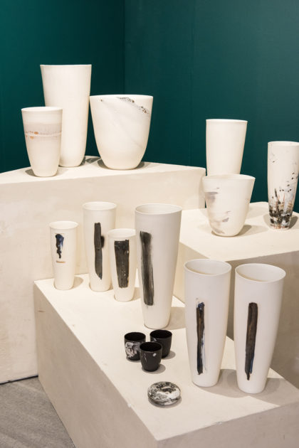 Market Art & Design, white design pieces exhibited in a booth with green walls
