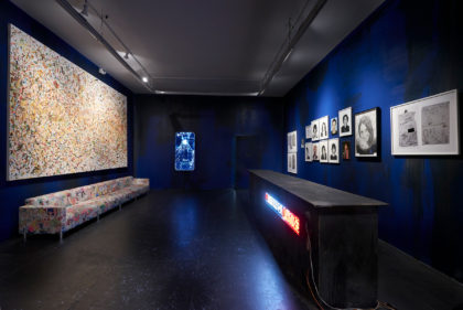 Installation view of photographs, paintings and a sculpture in a dark space