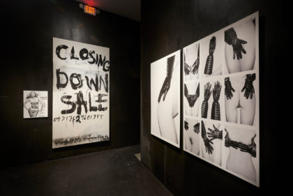 Installation view of photographs and posters on dark walls